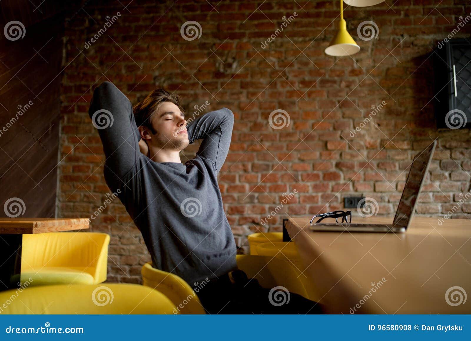 Het ontspannen rijpe zakenman doen leunen bij hal op laptop