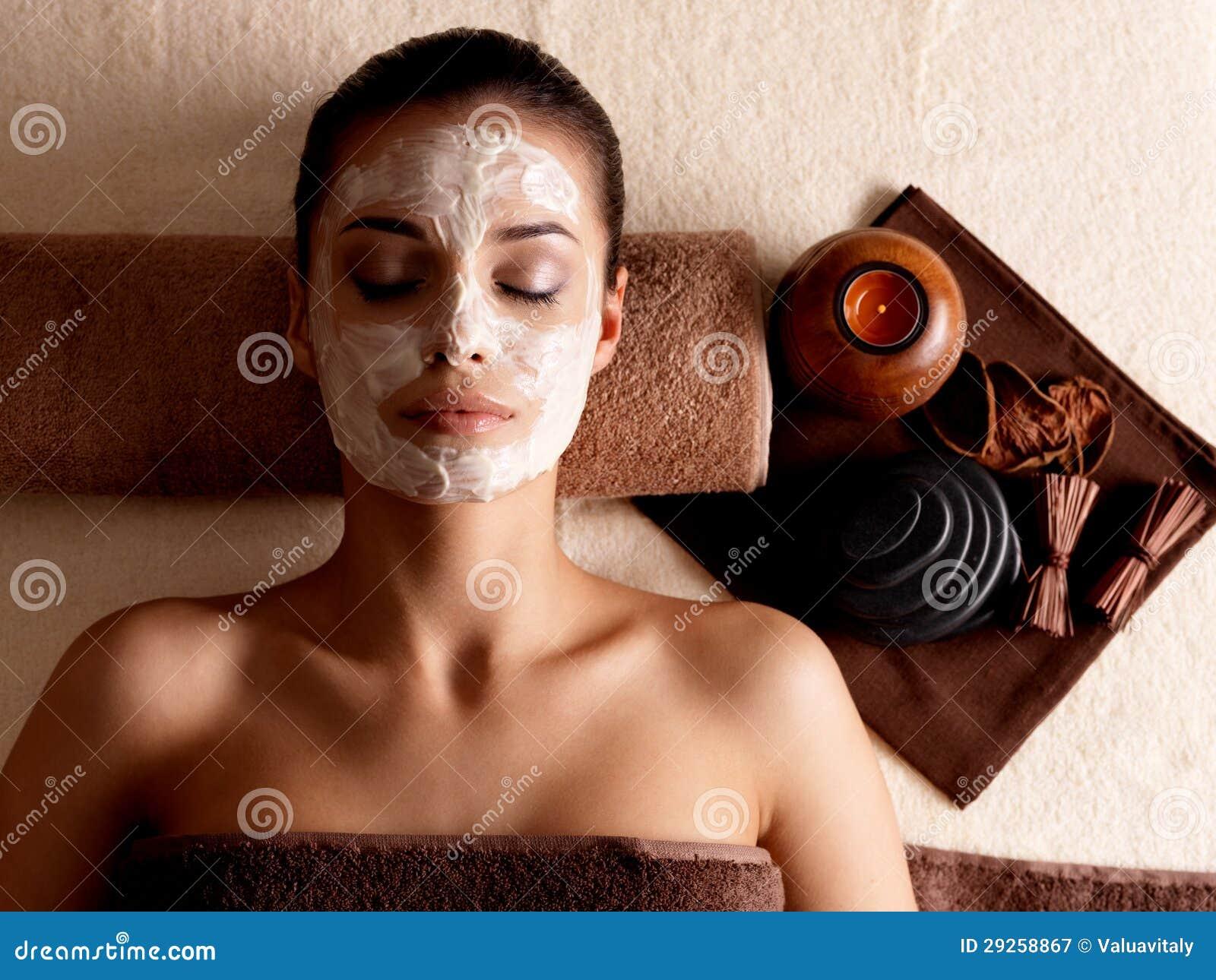 Het ontspannen van de vrouw met gezichtsmasker op gezicht bij schoonheidssalon