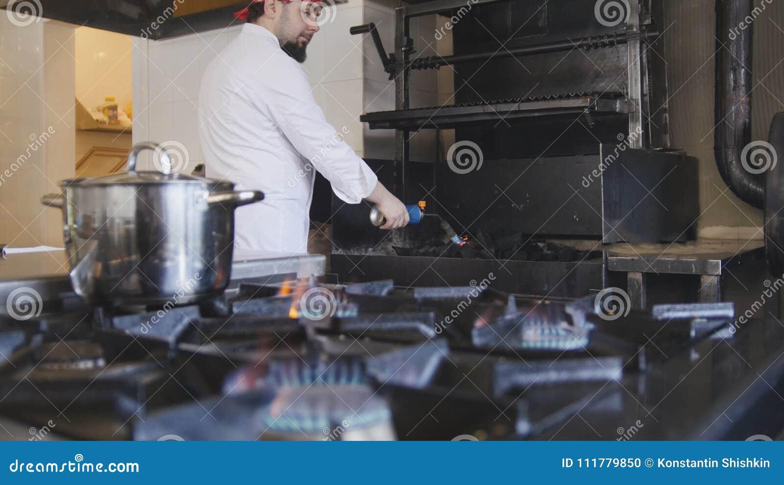 Het ontsteken van houtskool in de barbecueoven die een gasfornuis langzame motie gebruiken