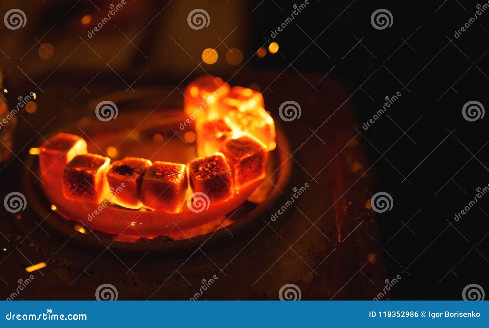 Het ontsteken van vierkante steenkool voor een waterpijp op een speciale oven met een hete spiraal
