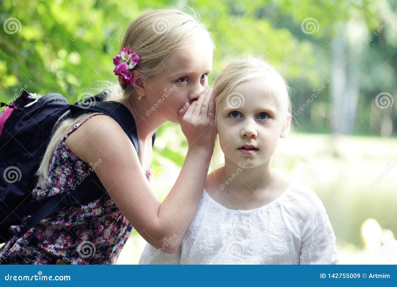 Het Oor van twee Zustergirls whisper in in openlucht Concept grap, geheim, fantasie, gesprek, gefluister verrassing Emotie van ge