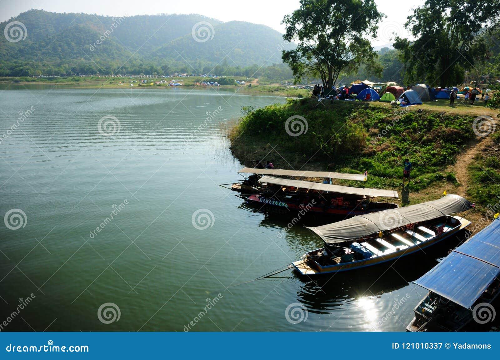 Het openlucht kamperen dichtbij meer met landende boot bij dok De toerist heeft velen comping activiteit