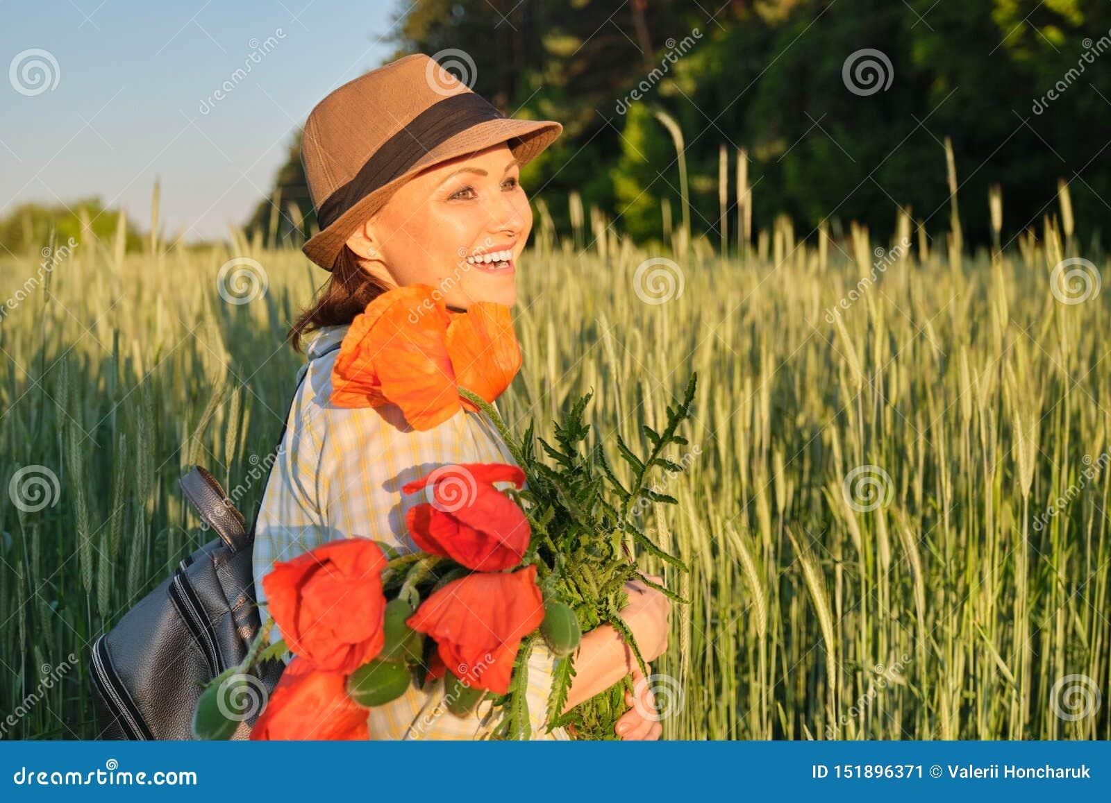 Het openluchtportret van een gelukkige rijpe vrouw met boeketten van rode papavers bloeit