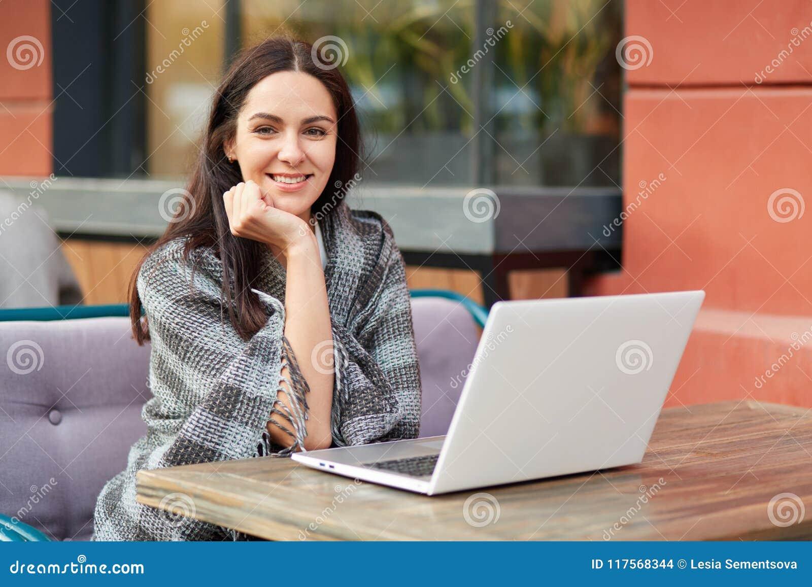 Het opgetogen mooie vrolijke vrouwelijke model freelancer, denkt over idee voor publicatie, gebruikt laptop computer, binnen doet