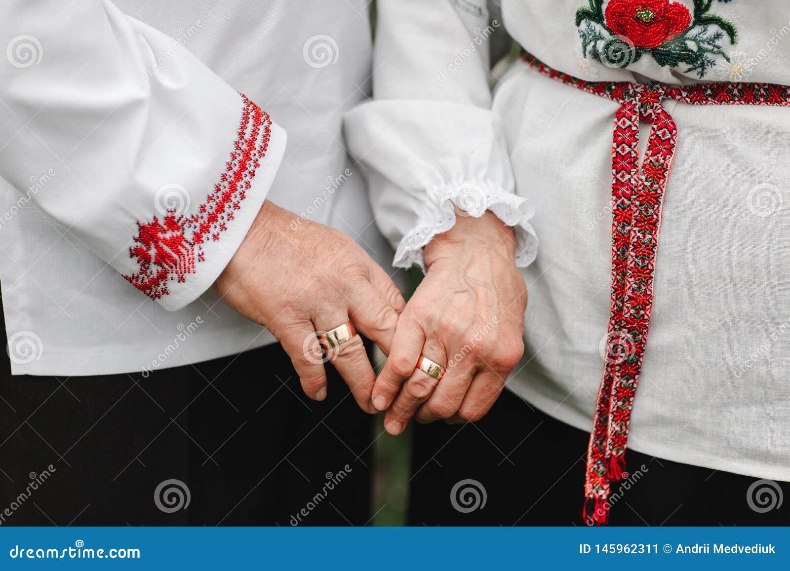 Het oude paar houdt handen Sluit omhoog van hogere man en vrouwenholdingshanden en in openlucht het lopen