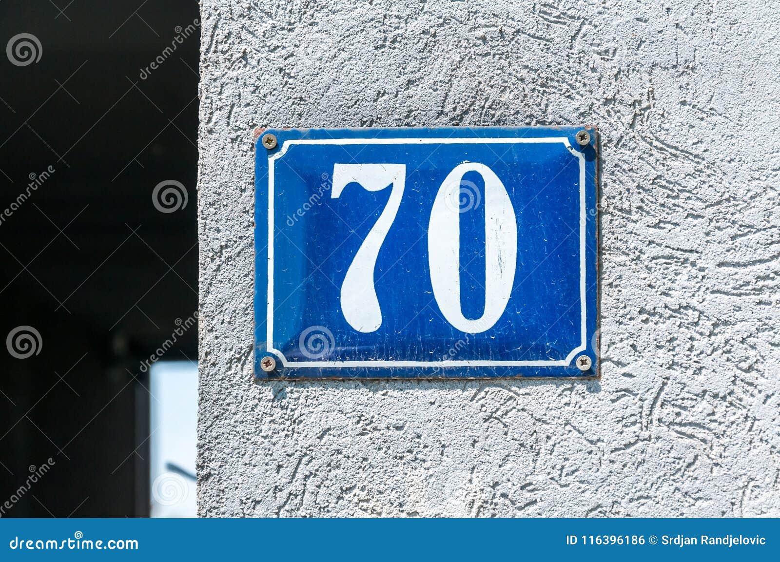 Het oude uitstekende metaal nummer 70 zeventig van het huisadres op de pleistervoorgevel van verlaten huis buitenmuur aan de stra