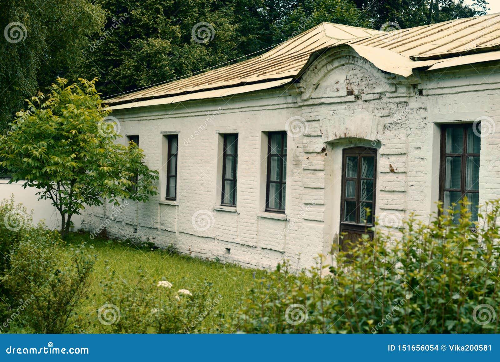 Het oude witte historische gebouw van één verdieping