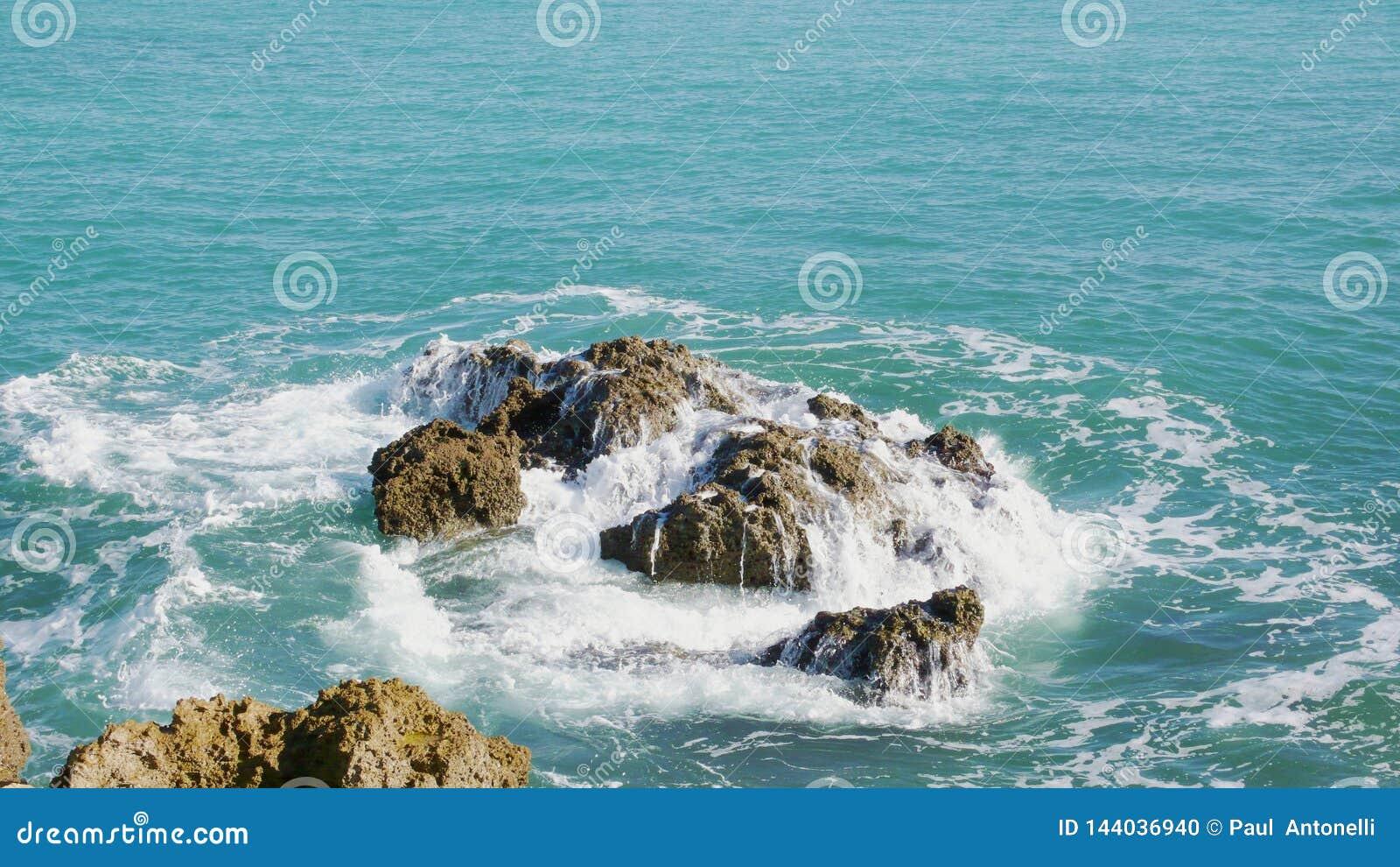 Het overzeese breken over sommige rotsen