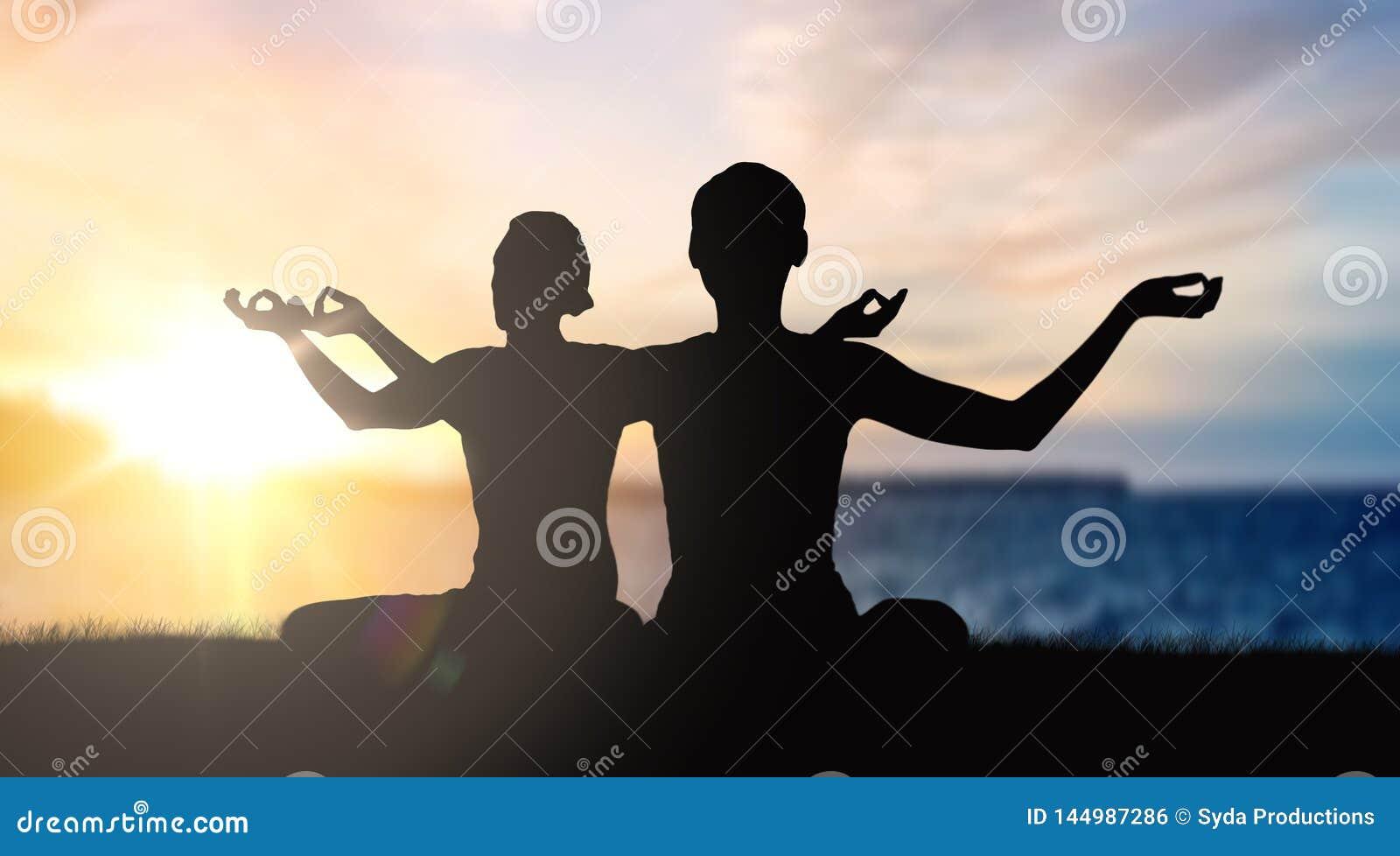 Het paar die yoga in lotusbloem doen stelt over zonsondergang