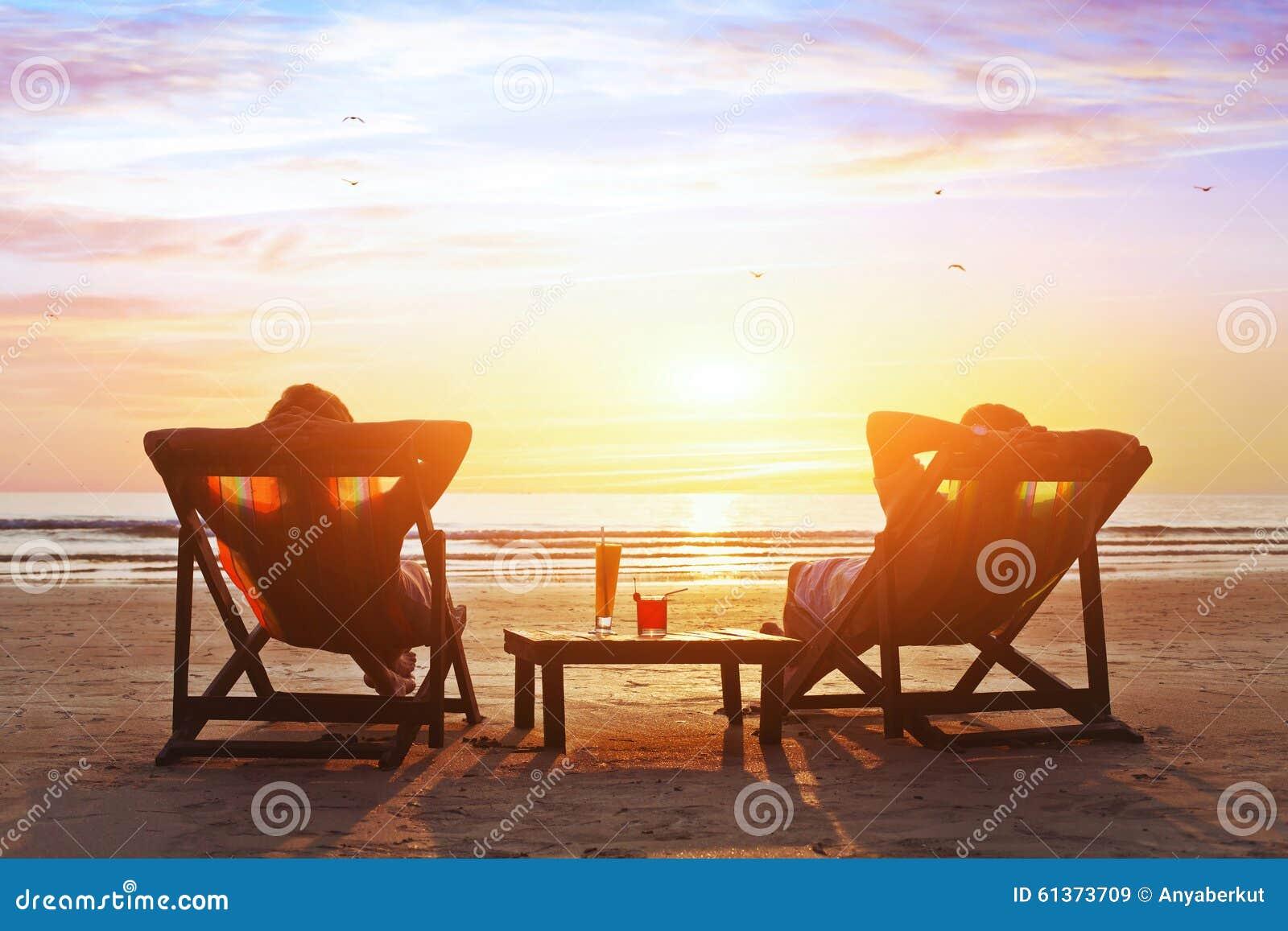 Het paar geniet luxe van zonsondergang op het strand