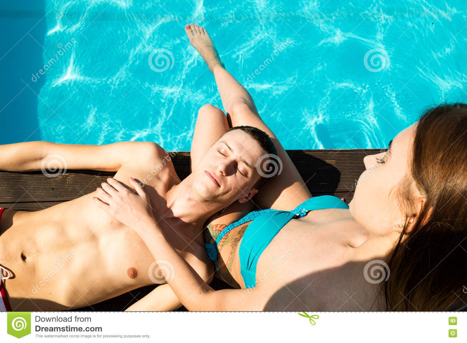Het paar heeft een rust in de pool met champagne zij glimlachen, koesteren en kussen
