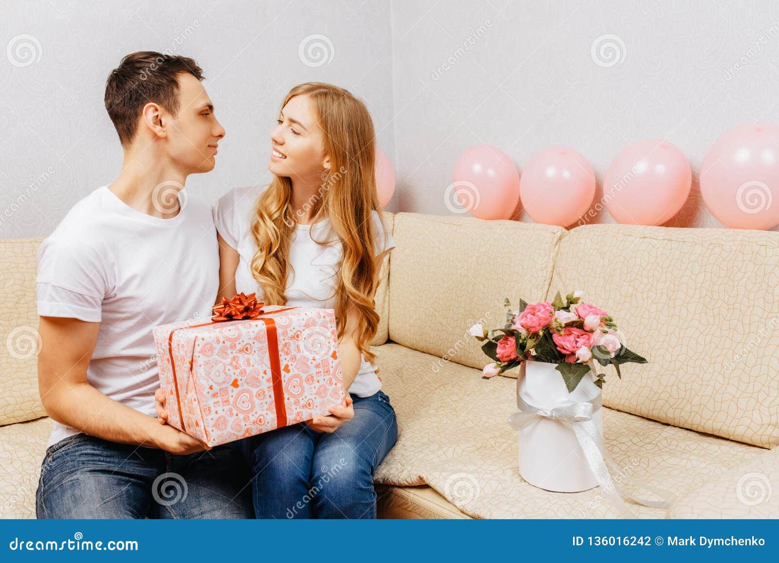 Het paar in liefde, mens geeft een gift, zit de vrouw thuis op de bank, concept de dag van vrouwen