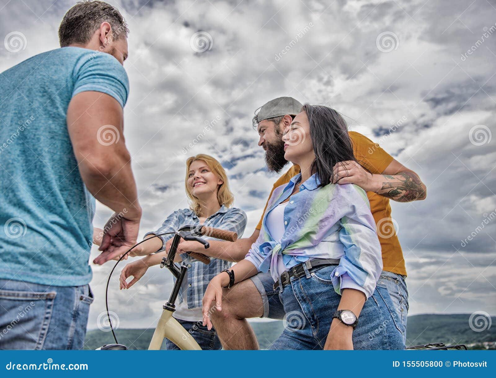 Het paar ontmoet vrolijke vrienden met fiets tijdens gang Het cirkelen moderne toestand en nationale cultuur Bedrijf modieuze jon