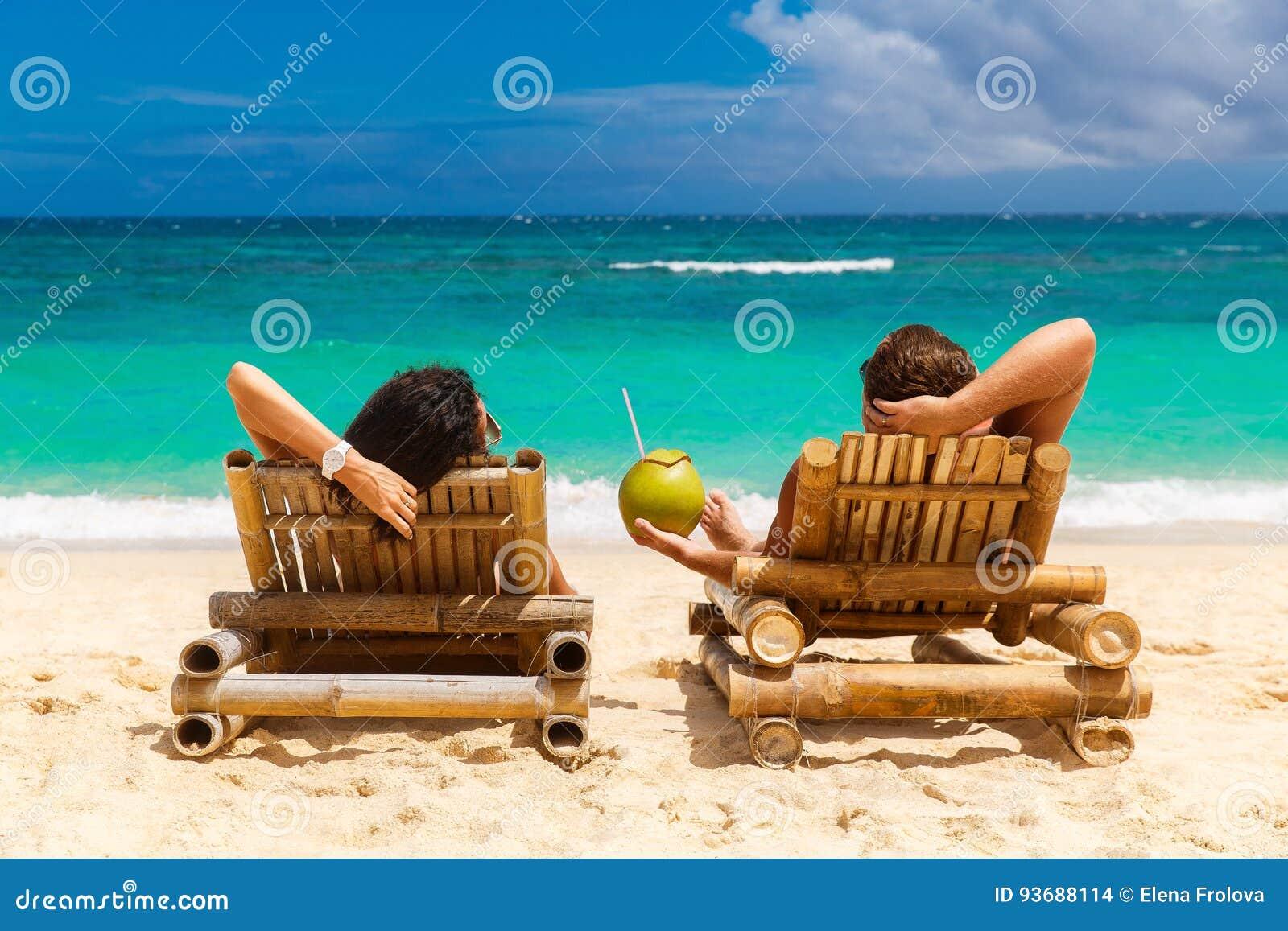 Het paar van de strandzomer op de vakantie van de eilandvakantie ontspant in de zon