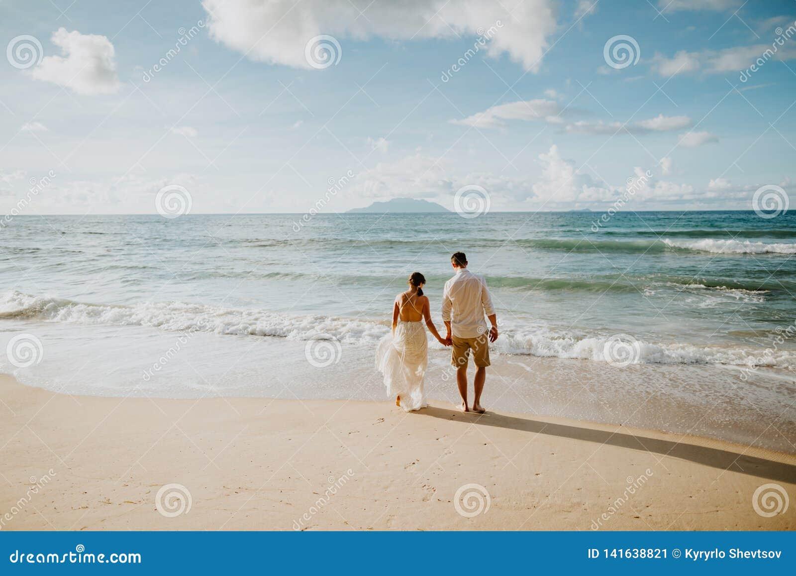Het paar van het wittebroodswekenhuwelijk op strand bij zonsondergang