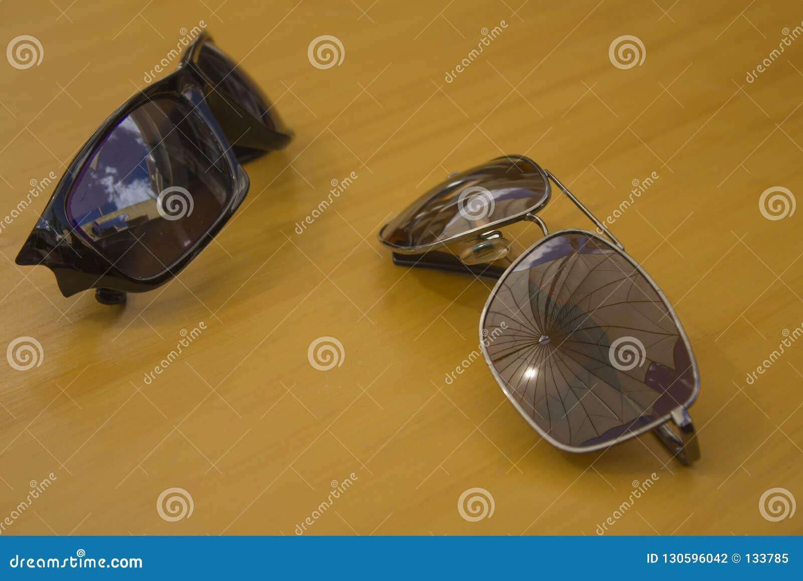 Het paar zonnebril ligt op een houten lijst