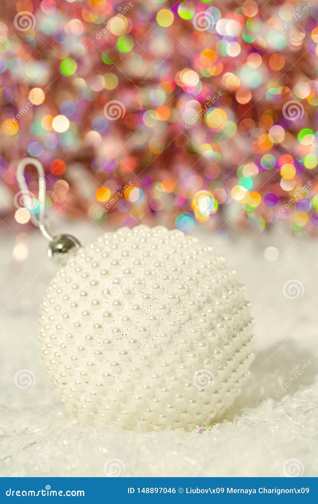 Het paarlemoerparels van de Kerstmisbal op een sneeuw en een mooie vage kleurrijke achtergrond van het schitteren bokeh met het g