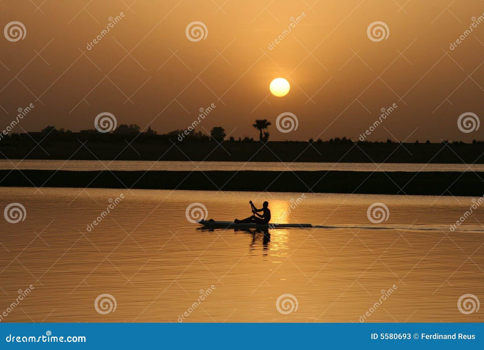 Het paddelen op het water bij zonsondergang