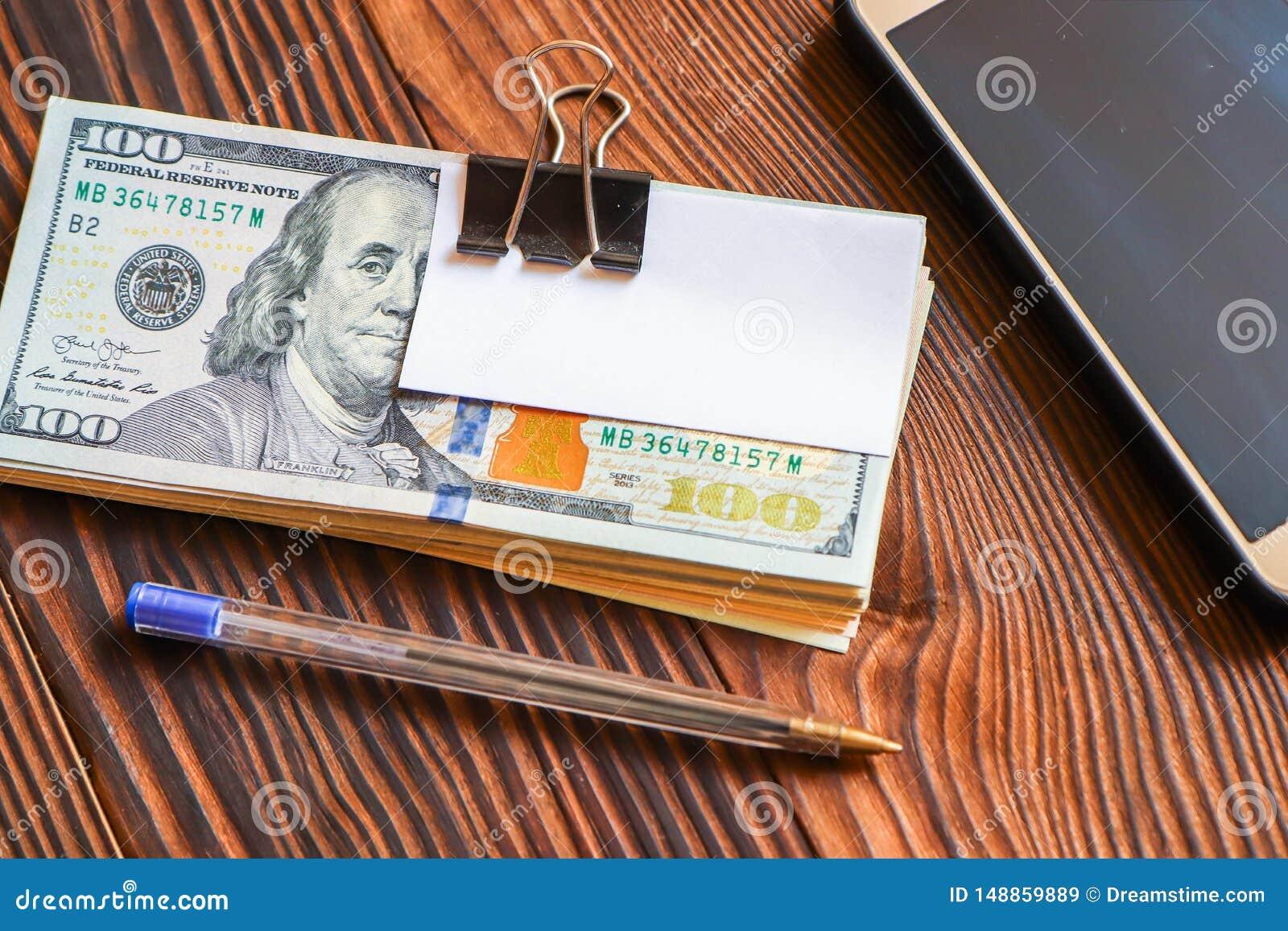 Het pak dollars telefoneert pen en document sticker voor uw tekst op houten achtergrond