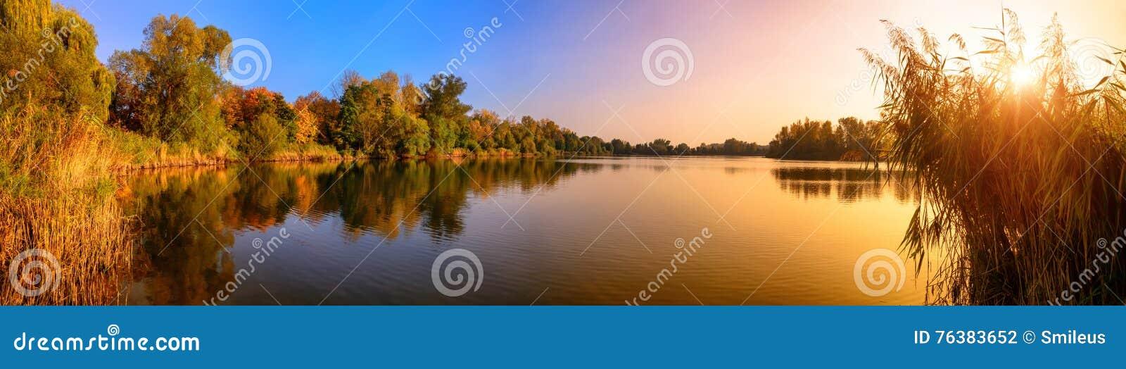 Het panorama van de meerzonsondergang in goud en blauw