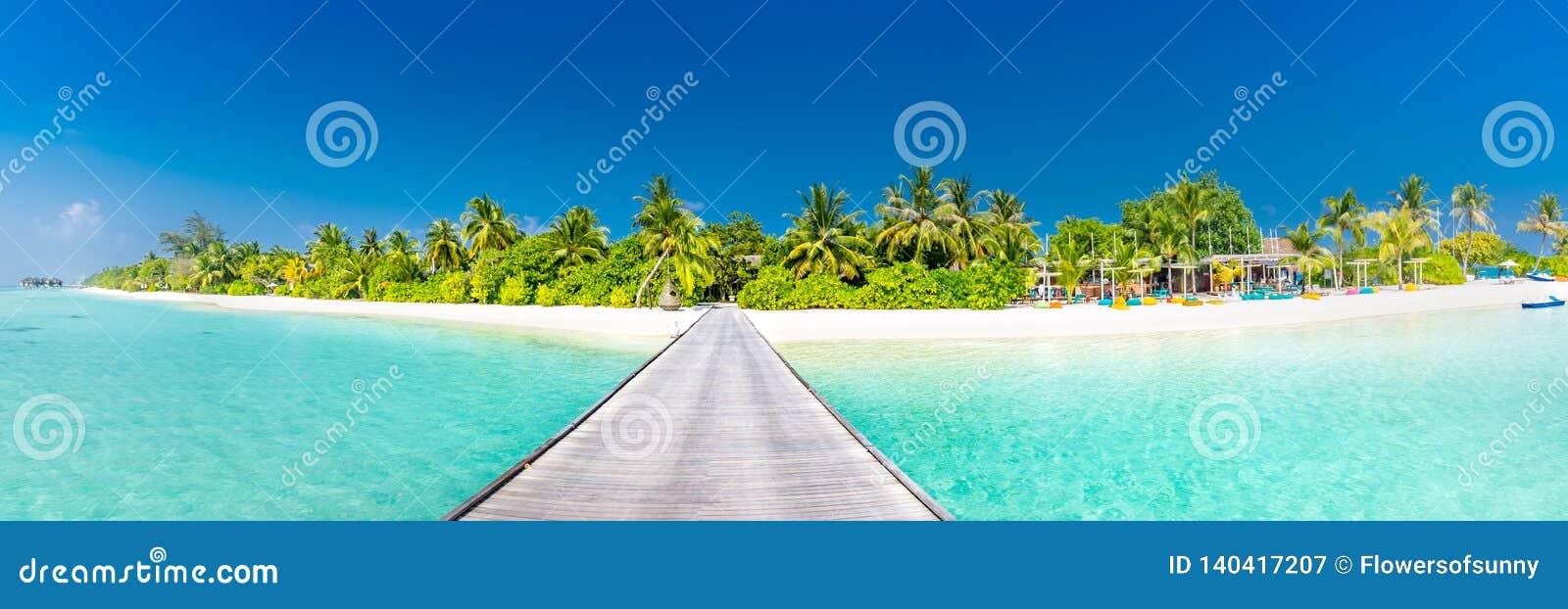 Het panorama van het het eilandstrand van de Maldiven Palmen en strandbar en lange houten pijlerweg Tropische vakantie en de zome