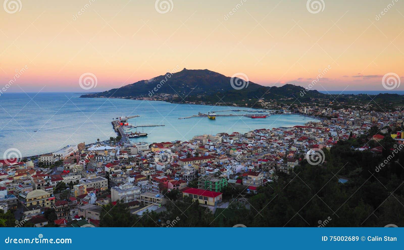 Het panorama van Zakynthos bij zonsondergang De klip van de Zantestad met veerbootharbou