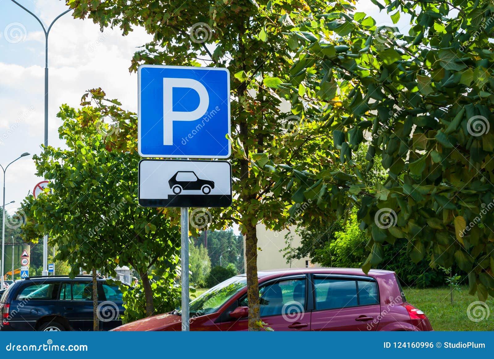 Het parkeren van het verkeerteken voor auto s op een achtergrond die van de stadsstraat tonen hoe te hun voertuigen correct te pl
