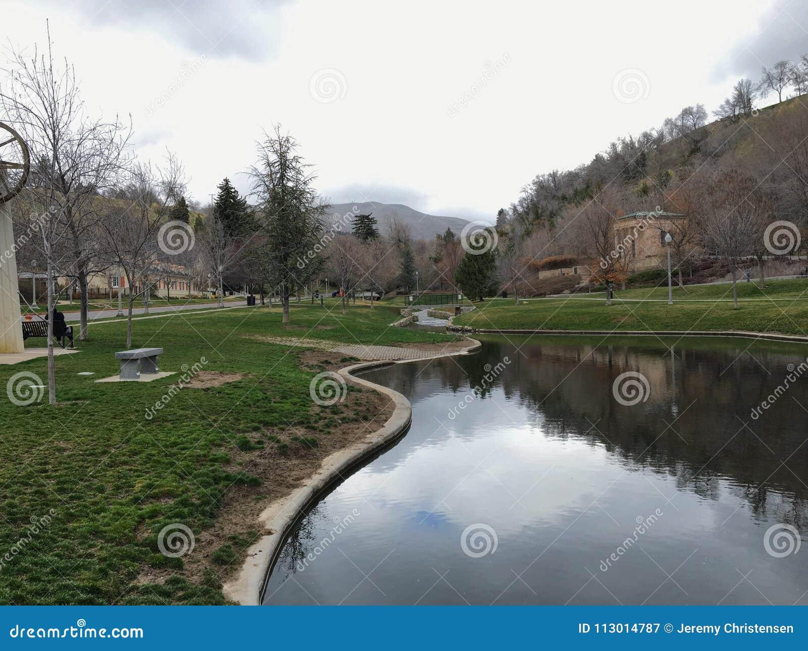 Het Parkmeningen van het geheugenbosje van Watervallen en stromen in een klein die vijver of een meer leiden door wegen wordt omr