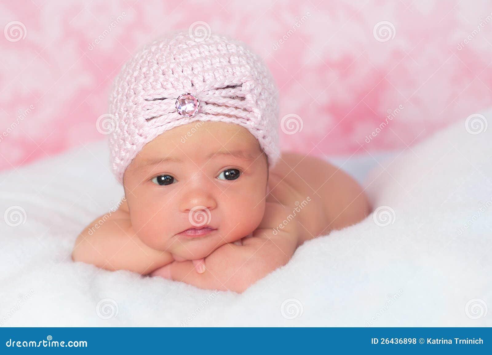 het pasgeboren meisje dat van de baby een roze hoed van de stijl van de vin draagt royalty vrije