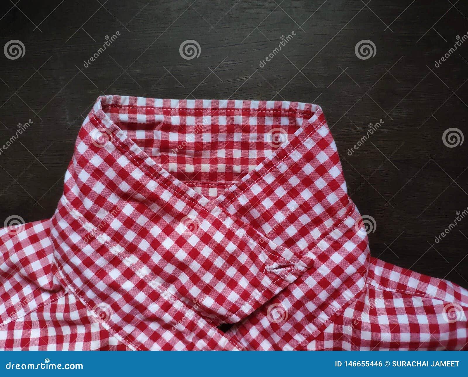 Het patroonkraag van de overhemdsplaid op een houten lijst wordt geplaatst die