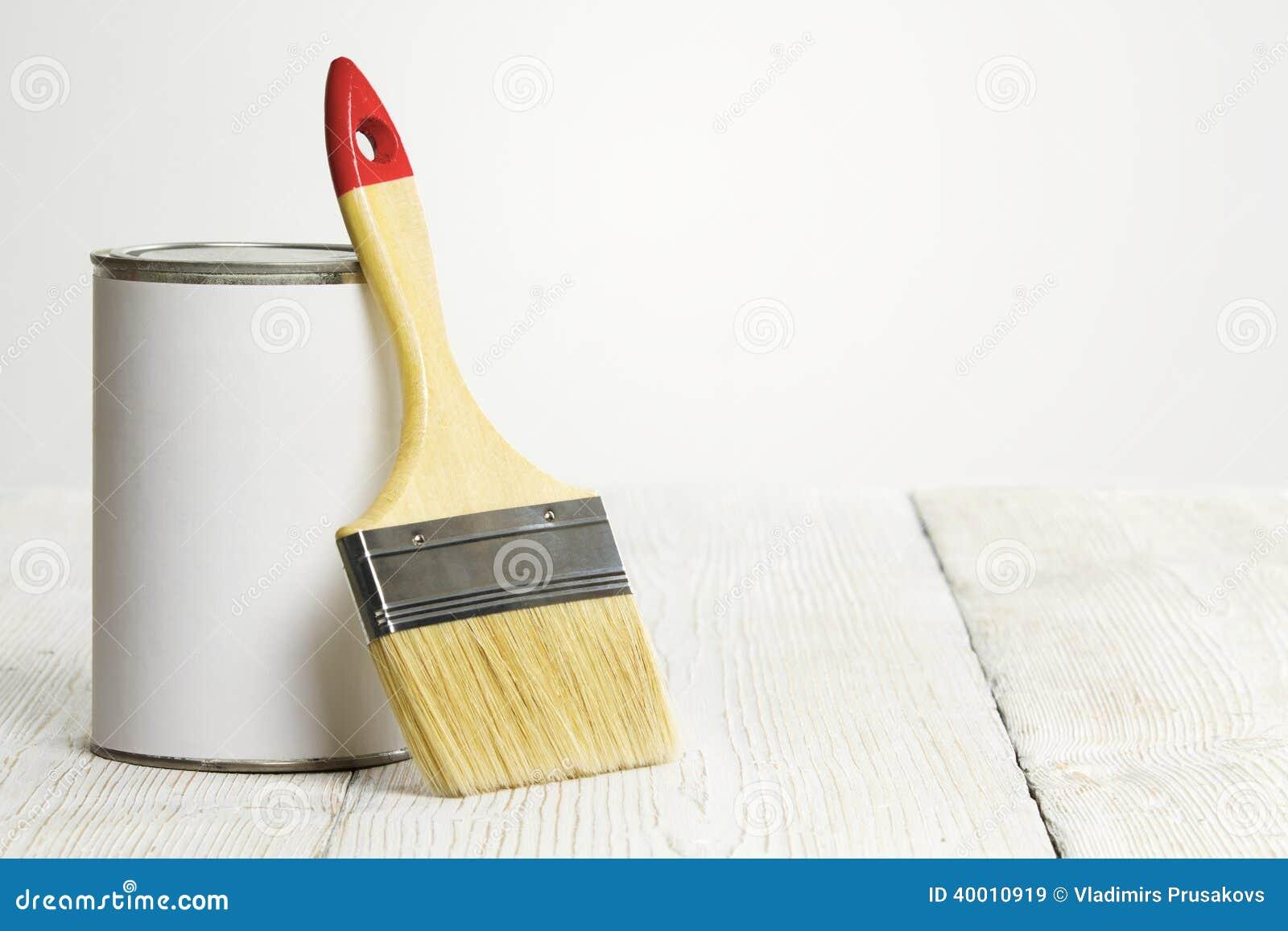 Het penseel en kan borstel en witte kleur op houten vloer