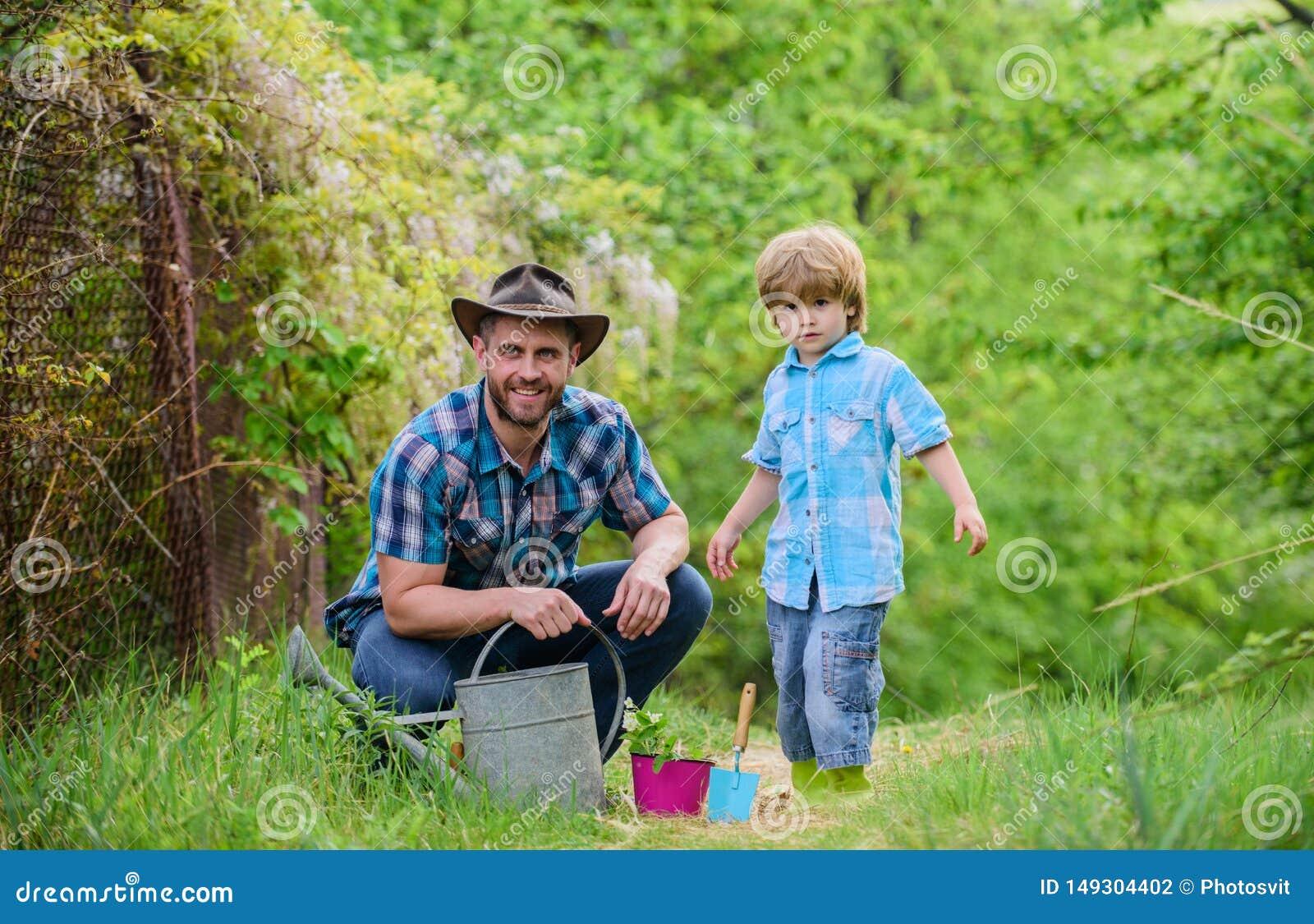 Het planten van bloemen Groeiende installaties Behandel Installaties Jongen en vader in aard met gieter Het tuinieren nieuwe hulp