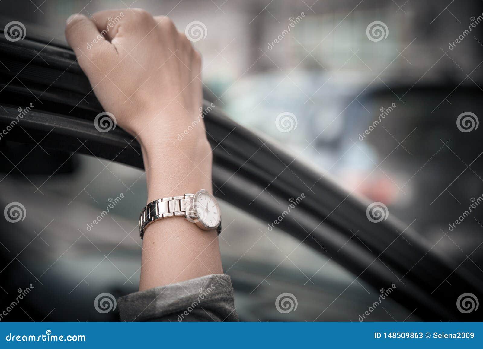Het polshorloge van vrouwen op de hand van het meisje Meisje die in zeven haasten, zich in een opstopping bevinden De tijd is gel