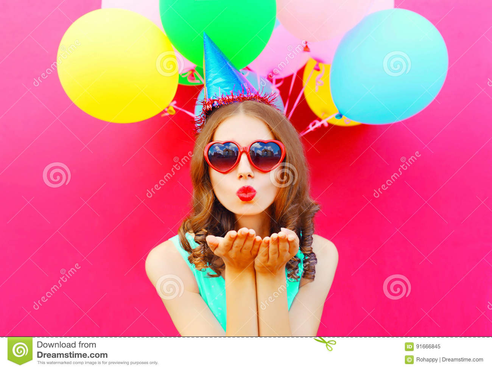Het portret de mooie vrouw in een verjaardag GLB is verzendt een luchtkus houdt een lucht kleurrijke ballons op roze achtergrond
