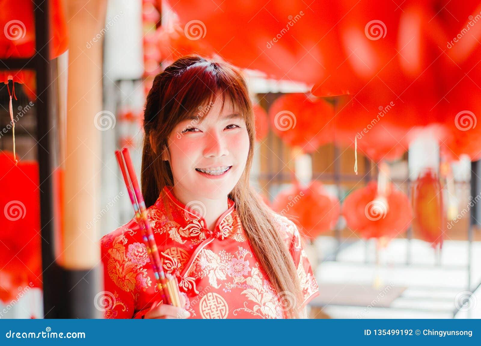 Het portret die de mooie Aziatische kleding van de vrouwenslijtage cheongsam omhoog charmeren kiest koopt de wierook, in het Chin
