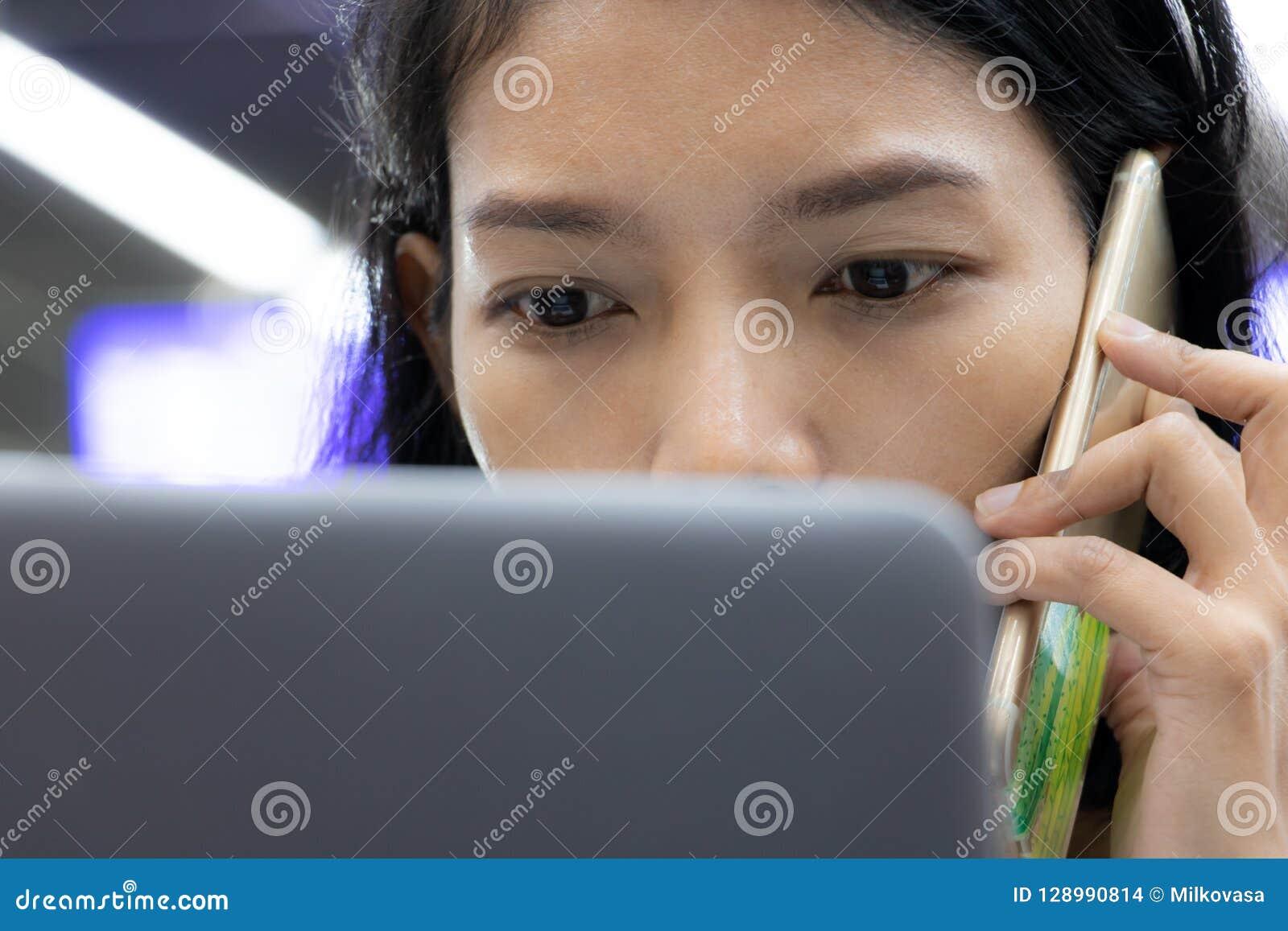Het portret die van jonge vrouw met telefoon roepen