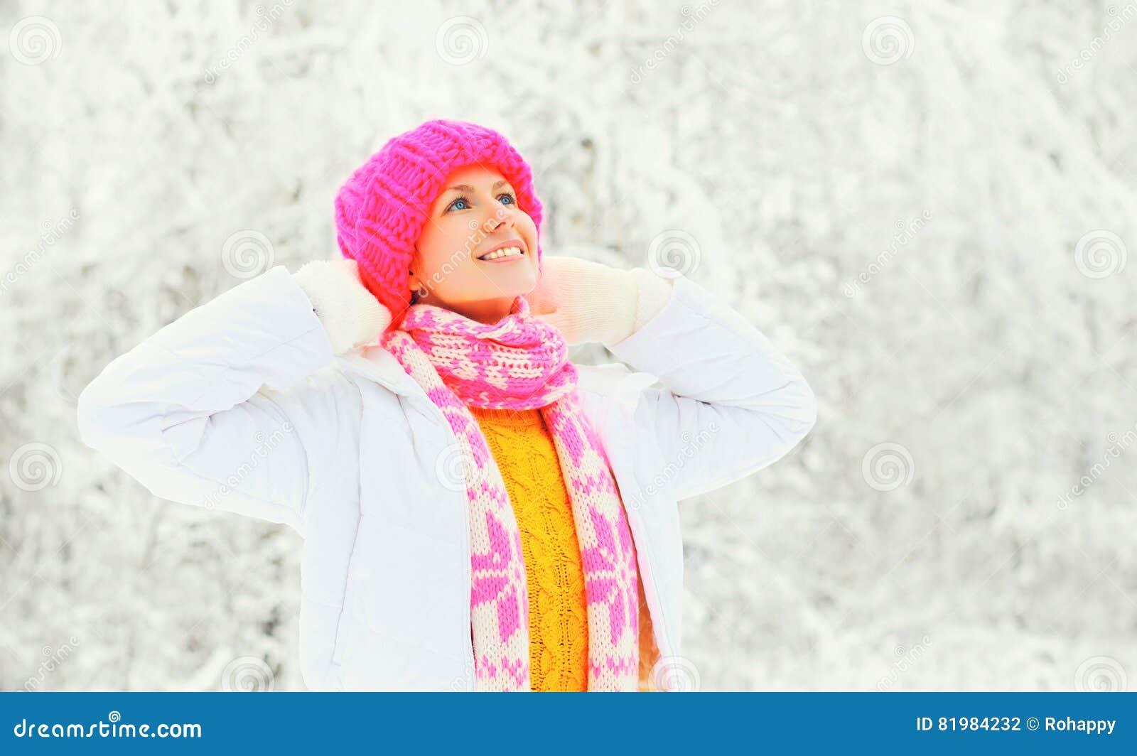 Het portret gelukkige vrouw die van de manierwinter een kleurrijke gebreide sjaal van de hoedensweater over sneeuwachtergrond dra