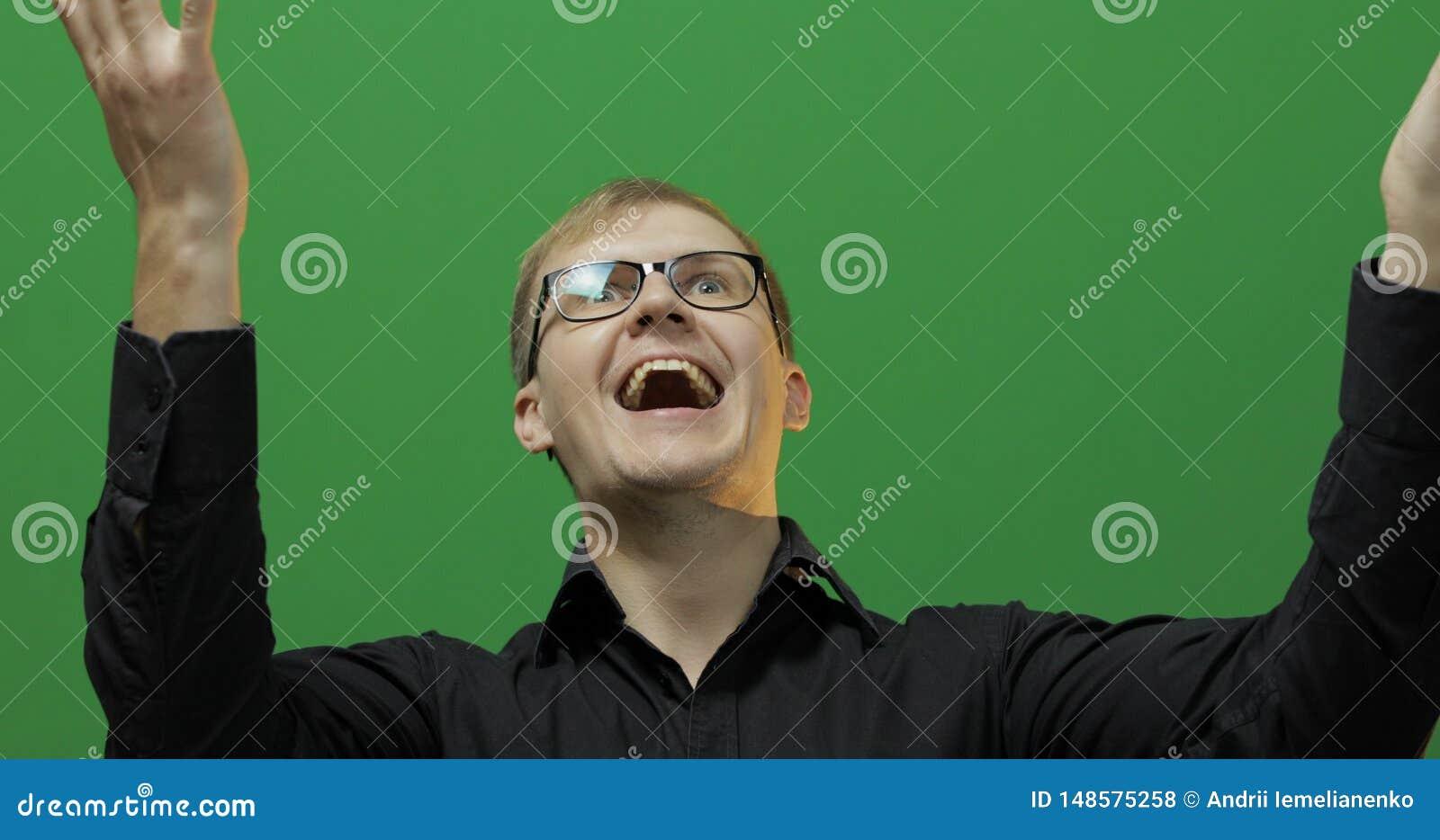 Het portret van de aantrekkelijke gelukkige jonge mens viert Het groene scherm Twee in: 1