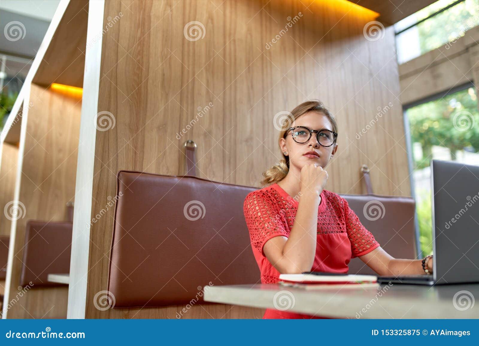 Het portret van de close-uplevensstijl van jonge peinzend blonde Kaukasische millennial blogger die glazen dragen die nota s over