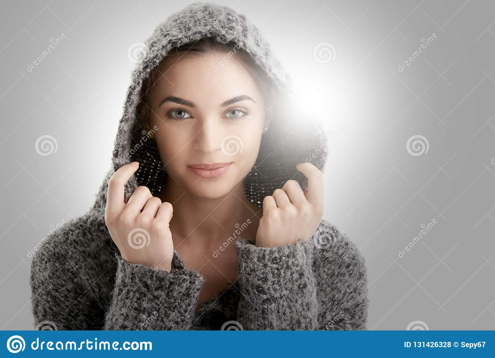 Het portret van de close-upstudio van het mooie jonge vrouw dragen hoodie terwijl het stellen bij geïsoleerde witte achtergrond