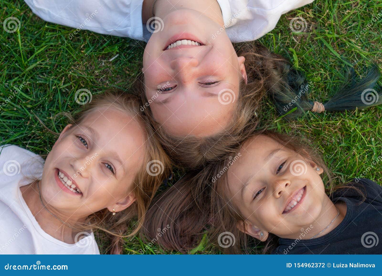 Het portret van de drie zusterszomer De leuke meisjes liggen op het gras en het glimlachen glimlachende kinderen openlucht Concep