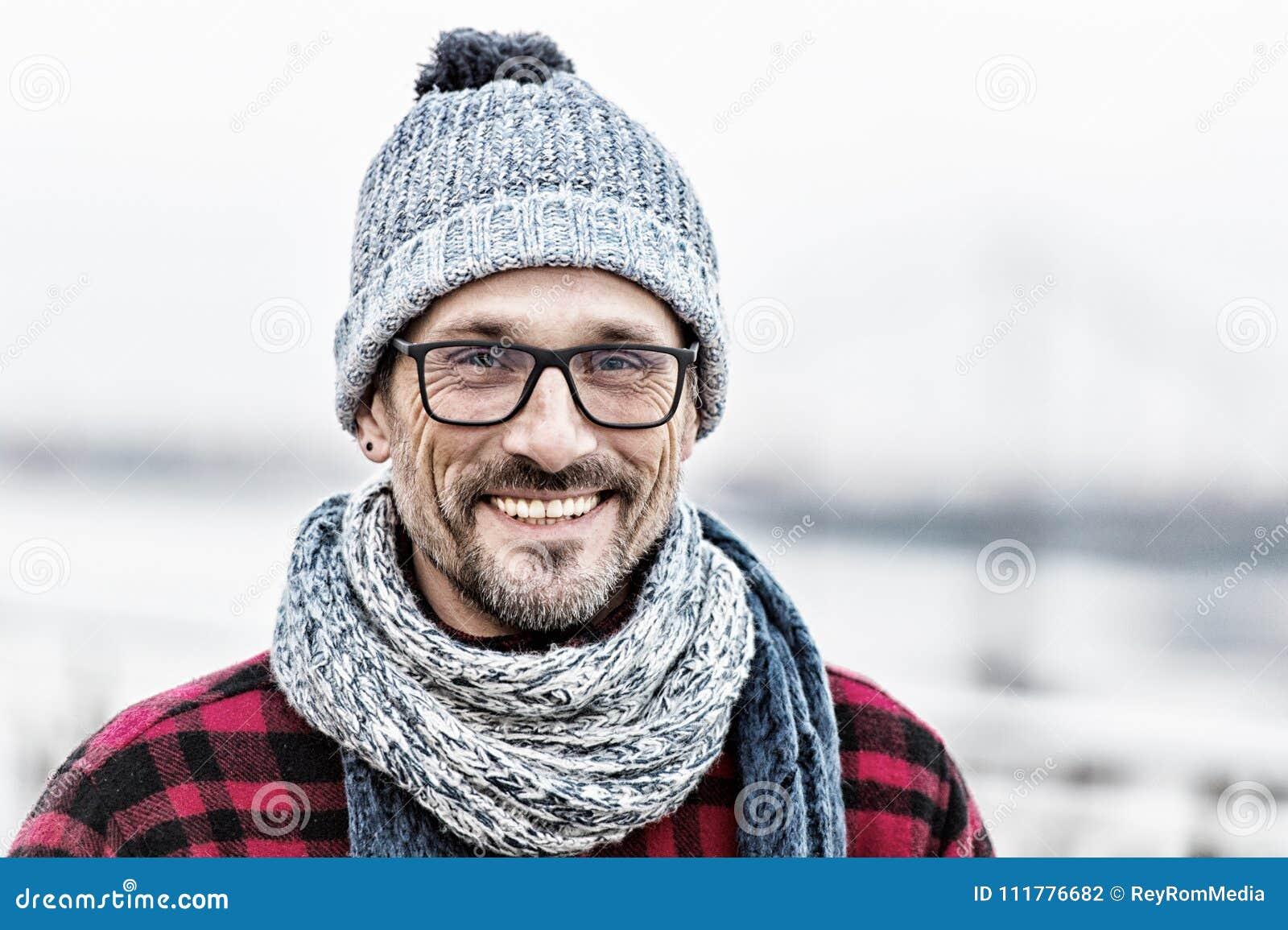 Het portret van de gelukkige stedelijke mens in de winter breide slijtage Portret van de mens in glazen en gebreide wit-blauwe sj