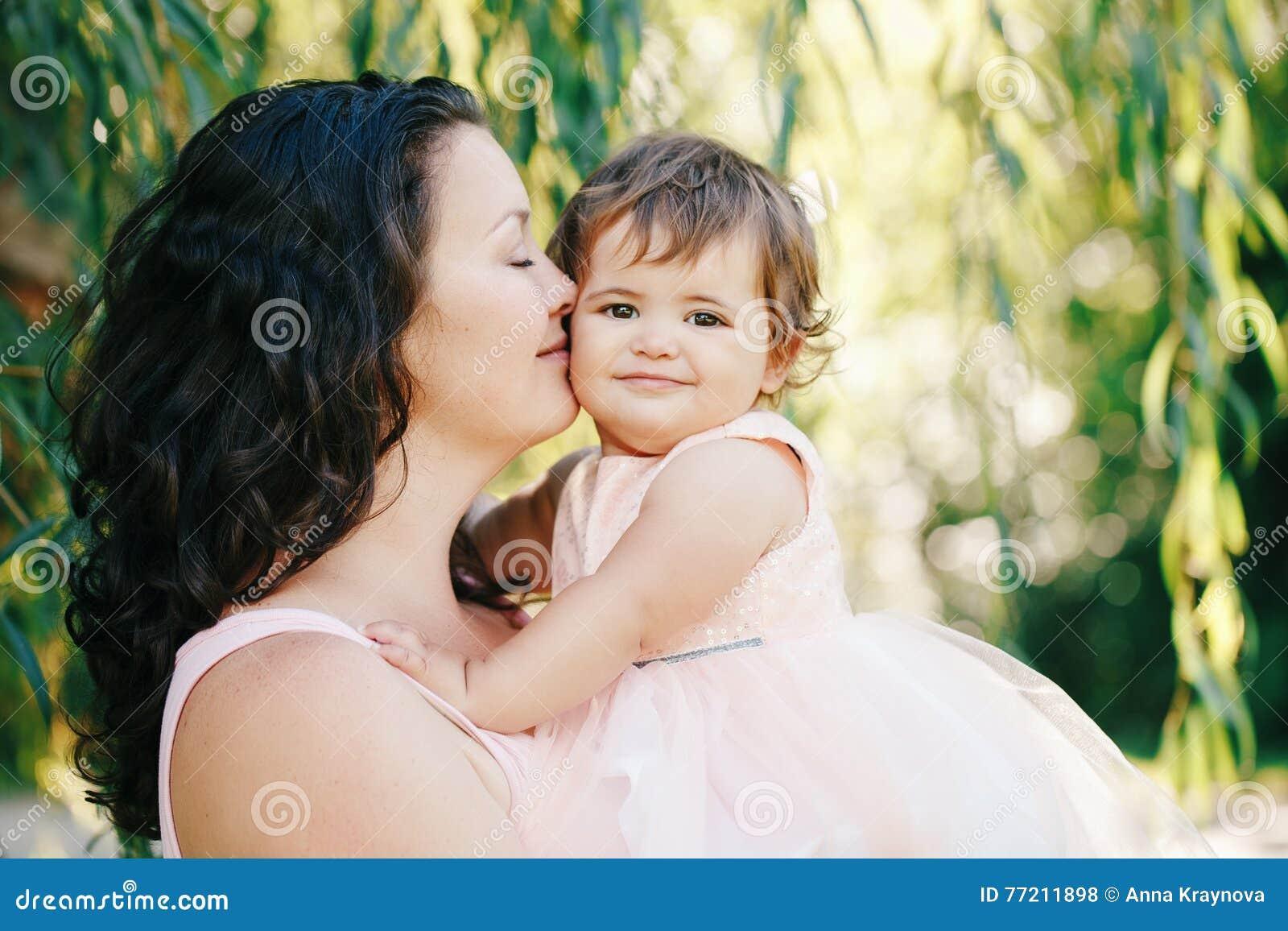 Het portret van de levensstijlgroep van mooie witte Kaukasische donkerbruine moederholding die dochter die in roze kleding koeste