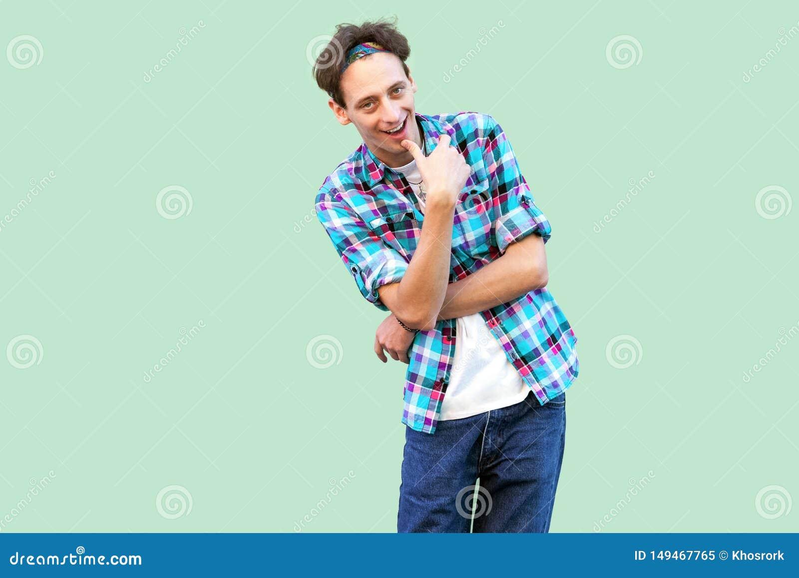 Het portret van de sluwe jonge mens in toevallig blauw geruit overhemd en hoofdband die en zich camera met het bedriegen bevinden