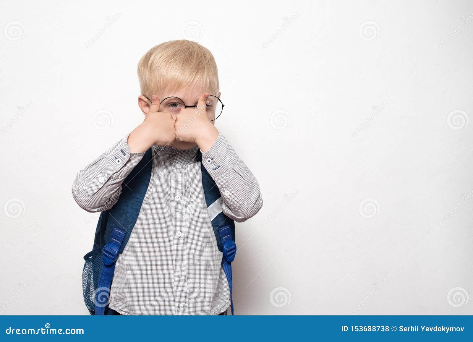 Het portret van een blonde jongen in glazen en met een schoolrugzak op een witte achtergrond toont een gebaarklasse Het concept v
