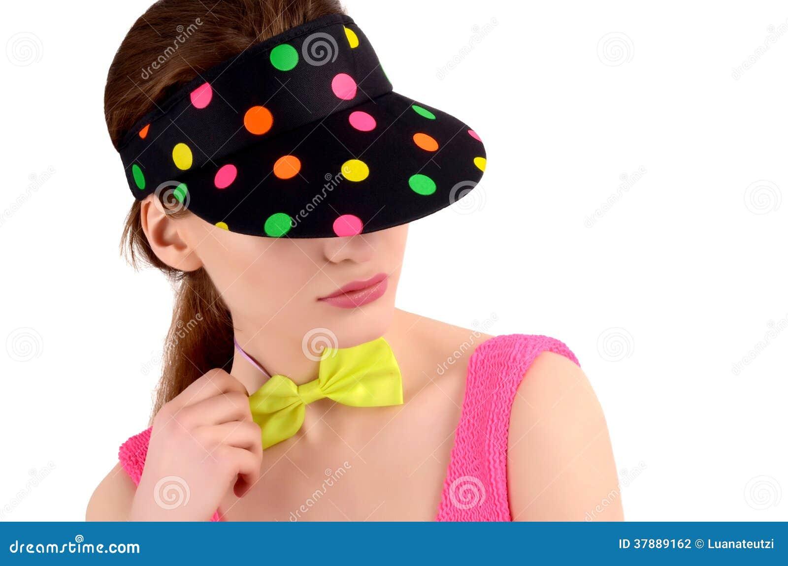 Het portret van een jonge vrouw die een kleurrijke polka draagt stippelde hoed en een neon groene bowtie.