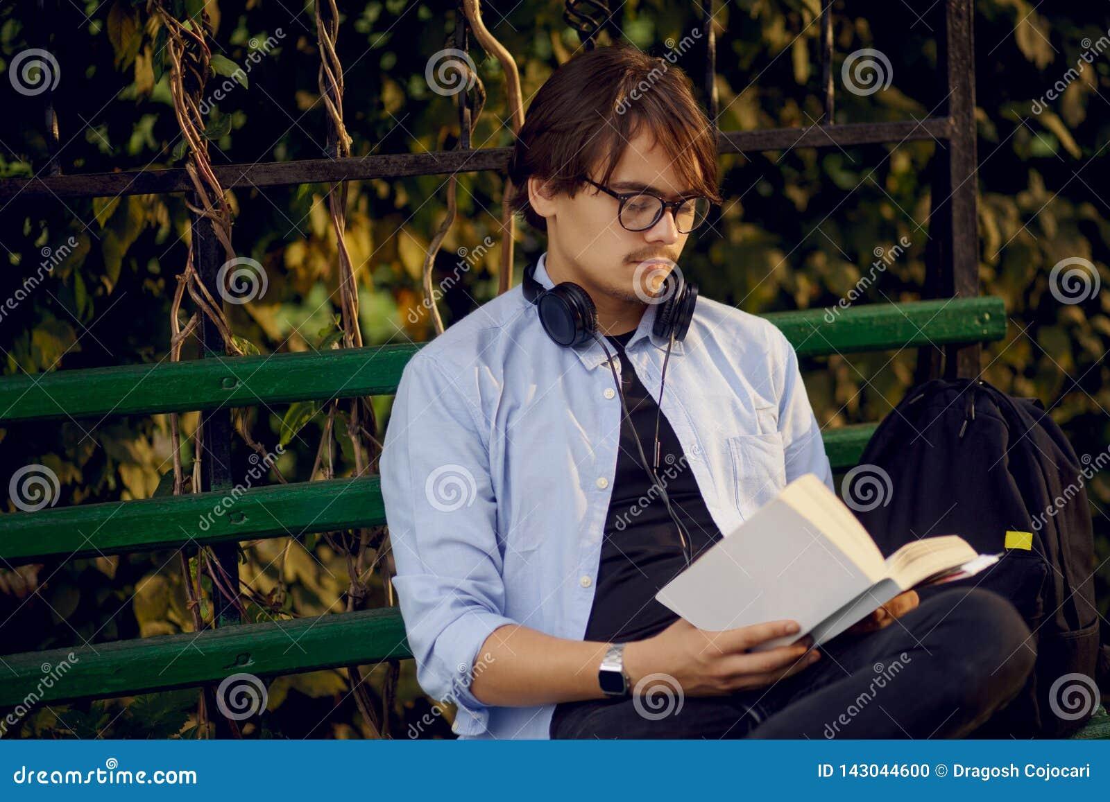 Het portret van een knappe jonge die mens in oogglazen en hoofdtelefoons, las een boek buiten, op een stedelijke parkachtergrond