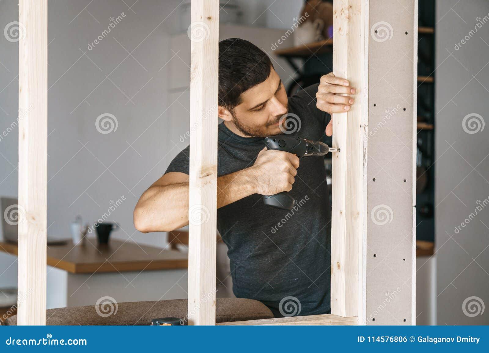 Het portret van een mens in huiskleren met een schroevedraaier in zijn hand bevestigt een houtconstructie voor een venster in zij