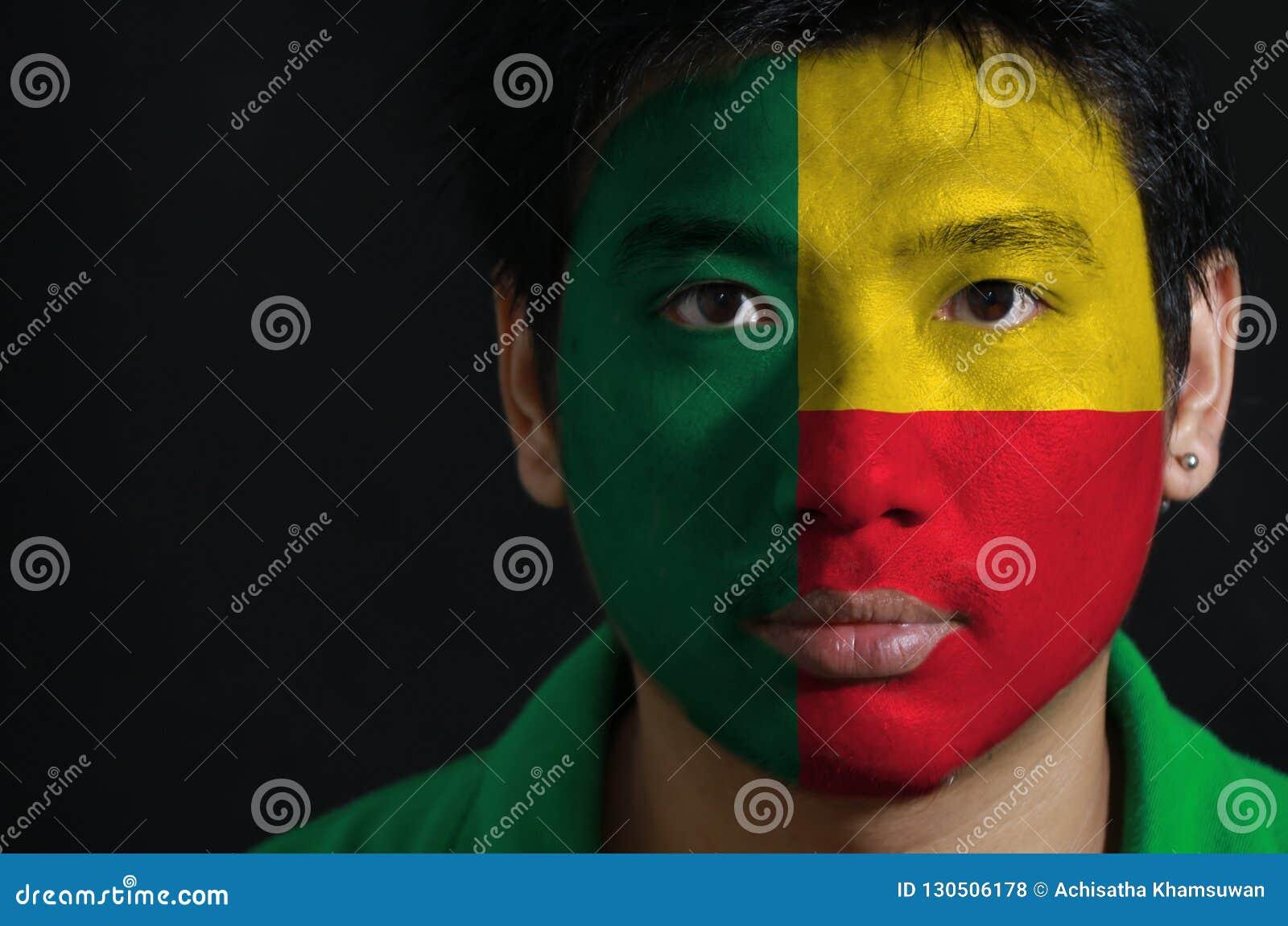 Het portret van een mens met de vlag van Benin schilderde op zijn gezicht op zwarte achtergrond