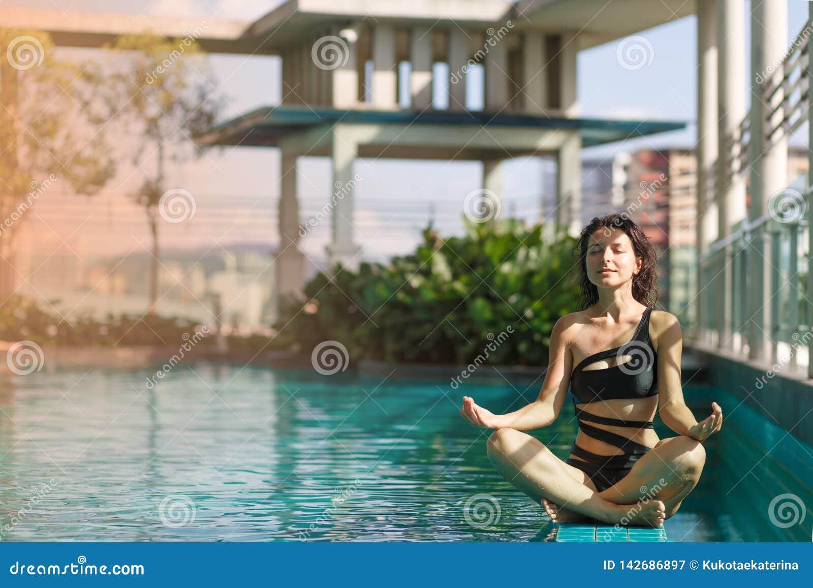 Het portret van een sexy meditatie Kaukasische vrouw in een zwempakzitting in lotusbloem stelt op de rand van een dakpool met gro